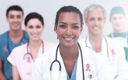 Composite image of breast cancer awareness ribbon. Breast cancer awareness ribbon against portrait of smiling female doctor with colleagues royalty free stock photography