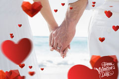 Composite image of bride and groom holding hands close up. Bride and groom holding hands close up against cute valentines message Stock Photography