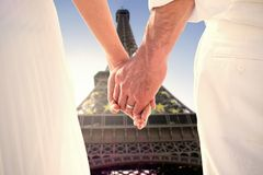 Composite image of bride and groom holding hands close up Stock Photo