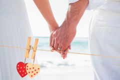 Composite image of bride and groom holding hands close up Royalty Free Stock Photo
