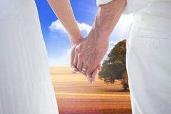 Composite image of bride and groom holding hands close up Stock Photos
