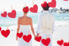 Composite image of bride and groom holding hands looking out to sea Royalty Free Stock Photos