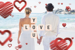 Composite image of bride and groom holding hands looking out to sea. Bride and groom holding hands looking out to sea against love you tiles royalty free stock photo