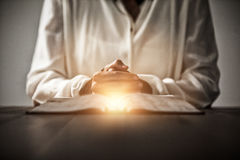 Composite image of bright spot of a flare. Bright spot of a flare against woman sitting at desk with bible Royalty Free Stock Photo