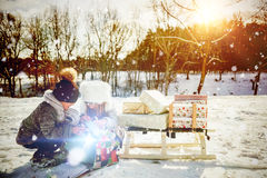 Composite image of brother and sister opening present while crouching at snow field. Brother and sister opening present while crouching at snow field against Royalty Free Stock Photos