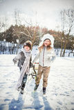 Composite image of brother and sister playing with sled on snow field Royalty Free Stock Image