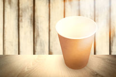 Composite image of brown cup over white background without cover. Brown cup over white background without cover against wood background Royalty Free Stock Photo