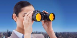 Composite image of brunette businesswoman looking through binoculars Stock Image