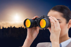 Composite image of brunette businesswoman looking through binoculars Stock Photos