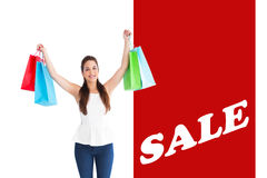Composite image of brunette in casual clothes holding shopping bags Stock Images