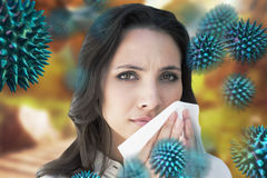 Composite image of brunette with a cold. Brunette with a cold against autumn scene royalty free stock photos