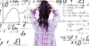 Composite image of brunette with hands on hair in front of sticky notes on wooden wall Royalty Free Stock Image