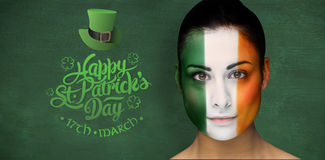 Composite image of brunette in irish face paint Royalty Free Stock Image