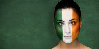 Composite image of brunette in irish face paint Stock Photos