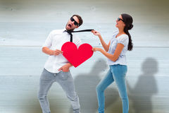 Composite image of brunette pulling her boyfriend by the tie Stock Photo