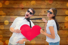 Composite image of brunette pulling her boyfriend by the tie holding heart Stock Photography