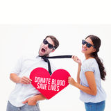 Composite image of brunette pulling her boyfriend by the tie holding heart Royalty Free Stock Photo