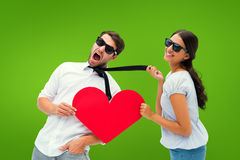 Composite image of brunette pulling her boyfriend by the tie holding heart Stock Image