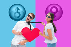 Composite image of brunette pulling her boyfriend by the tie holding heart Stock Photo