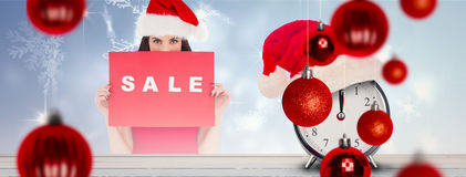 Composite image of brunette in red dress holding sale sign Stock Photography