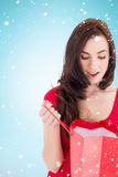 Composite image of brunette in red dress looking in shopping bag Royalty Free Stock Images