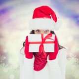 Composite image of brunette in red gloves and santa hat showing gift Stock Photos