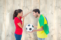 Composite image of brunette sending off a brazilian fan Royalty Free Stock Photo