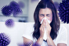 Composite image of brunette sneezing in a tissue. Brunette sneezing in a tissue against virus royalty free stock photography