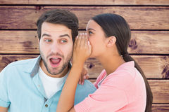 Composite image of brunette whispering secret to her boyfriend Stock Image