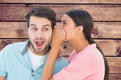 Composite image of brunette whispering secret to her boyfriend. Brunette whispering secret to her boyfriend against wooden planks background stock image
