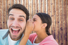 Composite image of brunette whispering secret to her boyfriend Royalty Free Stock Photography