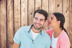 Composite image of brunette whispering secret to her boyfriend Stock Photos