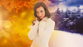 Composite image of brunette in white jumper smiling at camera Royalty Free Stock Photo