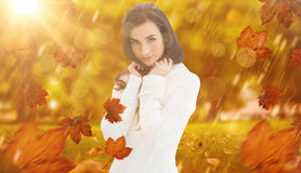 Composite image of brunette in white jumper smiling at camera Stock Photo
