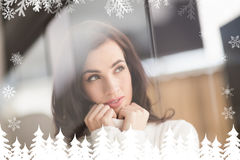 Composite image of brunette in white wool jumper thinking Royalty Free Stock Photos
