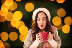 Composite image of brunette in winter clothes holding hot drink Royalty Free Stock Photo