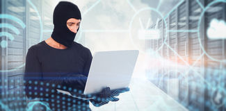 Composite image of burglar with balaclava hacking a laptop Royalty Free Stock Photo
