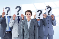 Composite image of business colleagues hiding their face with question mark sign Royalty Free Stock Photo