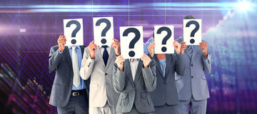 Composite image of business colleagues hiding their face with question mark sign Royalty Free Stock Photos