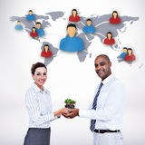 Composite image of business colleagues holding plant and looking at camera Stock Images