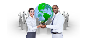 Composite image of business colleagues holding plant and looking at camera Royalty Free Stock Image