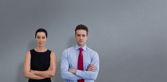 Composite image of business colleagues posing with crossed arms. Business colleagues posing with crossed arms  against grey background Royalty Free Stock Photography