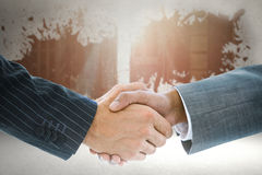 Composite image of business handshake against background Stock Photo
