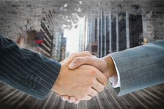 Composite image of business handshake against cityscape Stock Photography