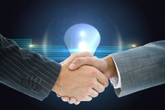 Composite image of business handshake against shiny light bulb Royalty Free Stock Image