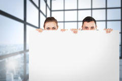 Composite image of business partners hiding behind a sign Royalty Free Stock Image