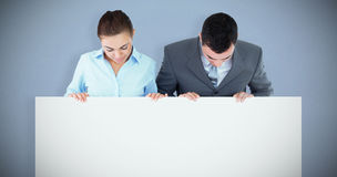 Composite image of business partners looking down at sign they are holding royalty free stock image