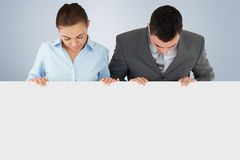 Composite image of business partners looking down at sign they are holding Royalty Free Stock Images
