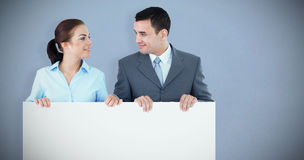 Composite image of business partners looking at each other while holding sign together stock image