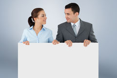 Composite image of business partners looking at each other while holding sign together Stock Images